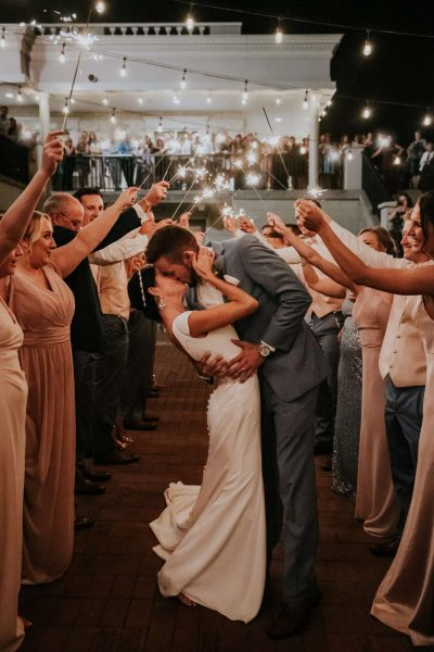 Groom kisses bride under a canopy of sparklers