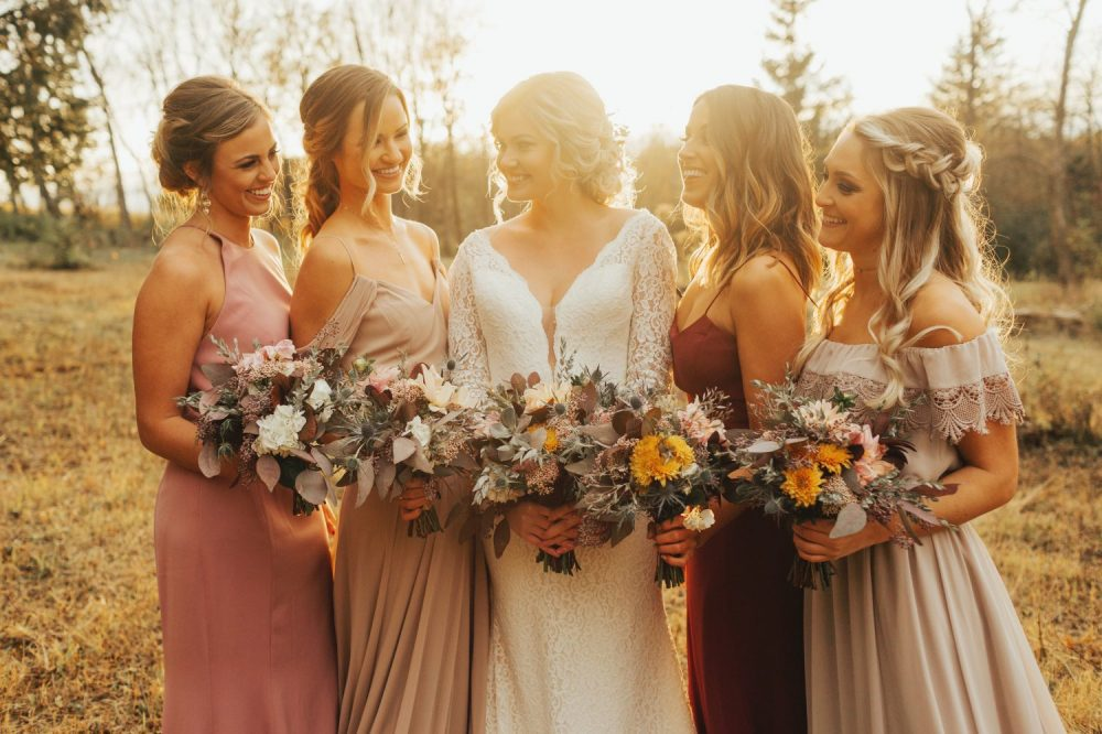 Bride and bridesmaids at sunset holding their country chic bouquets by Bank of Flowers