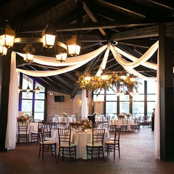 Draped linen with handing flowers over tables at wedding reception