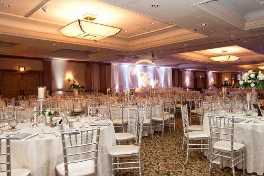 Monogram lighting behind head table at wedding reception