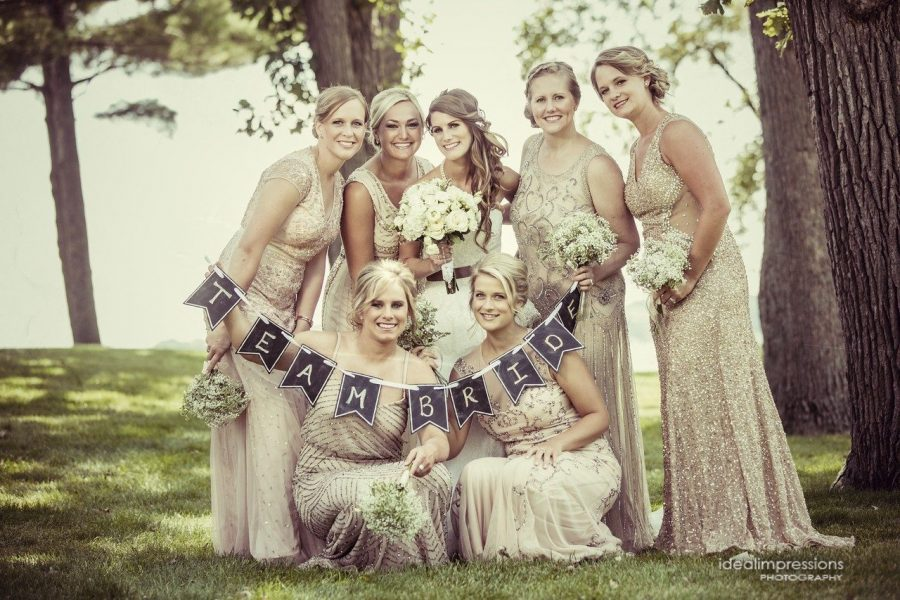 Bride and her bridesmaid pose with sign | Ideal Impressions Photography