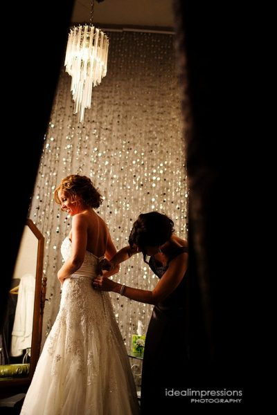Bride standing in elegant dressing room having her gown buttoned up | Ideal Impressions Photography