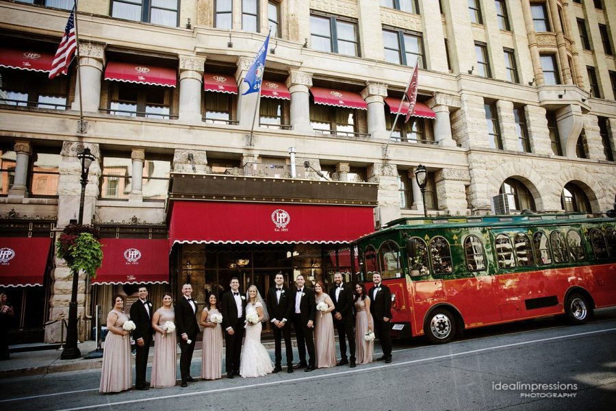 wedding party poses outside of the historic Pfister Hotel in Milwaukee, WI | Ideal Impressions Photography