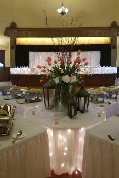 Accent table with flowers and uplighting by buffet table at Wedding Reception in Hartford, WI | Chandelier Ballroom