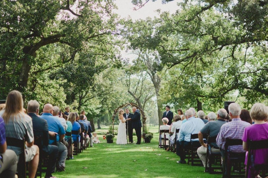 Wedding ceremony under a canopy of trees at the Watertown Country Club
