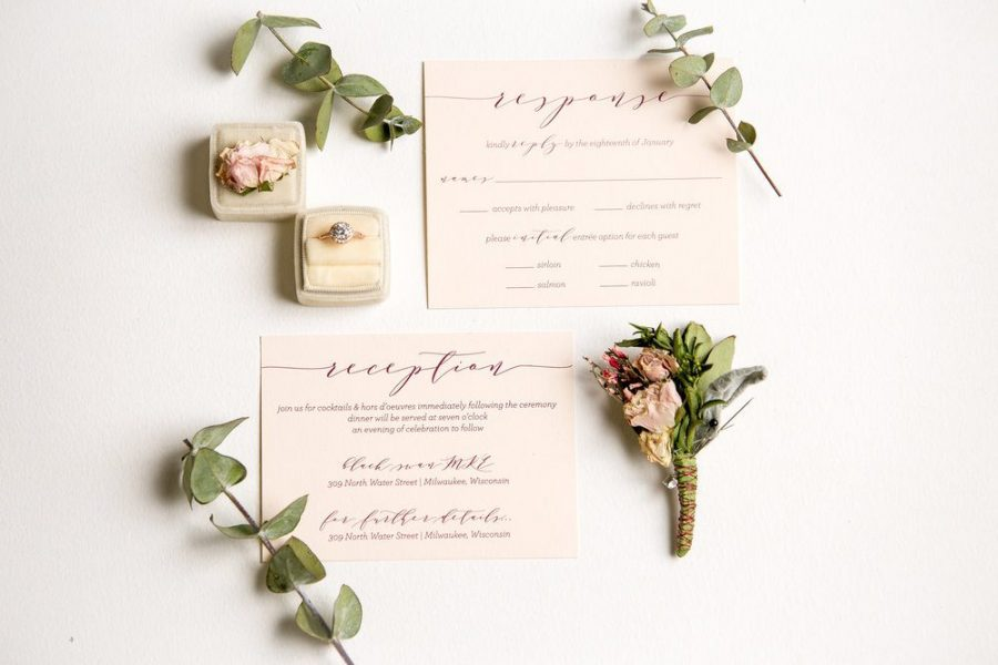 Personalized wedding invitations laid out flat with boutonniere and other accent pieces