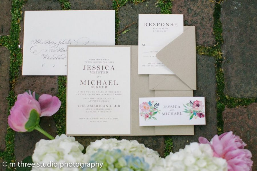 Display of a specific wedding's invitations and other related printed material with flowers to accent