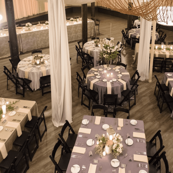 Ceiling drapes, decorated table with linens and centerpieces done with varied table shapes and sizes at the Pritzlaff.