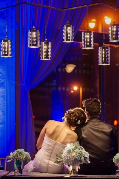 Wedding couple sitting together looking at the creative lighting and draping with up-lighting.
