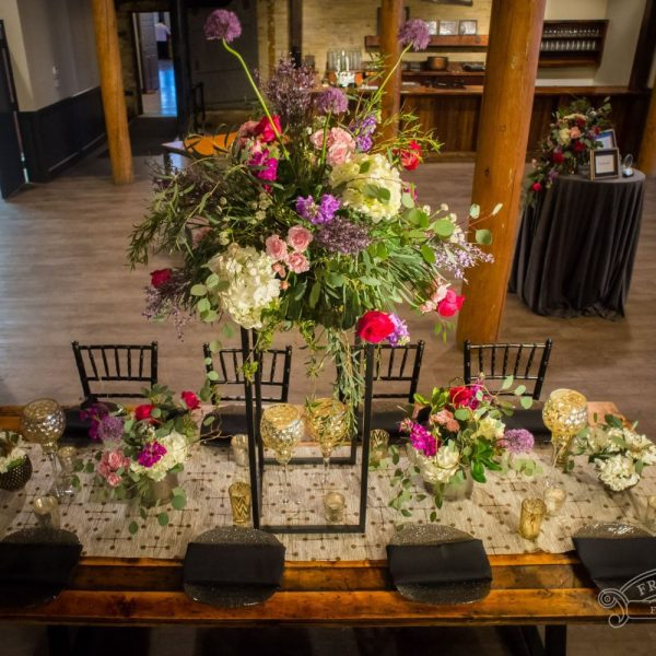 Gorgeous reception table with black accents, elevated centerpiece and table level centerpieces of purple, red, pink, cream and lots of greenery at the Pritzlaff.