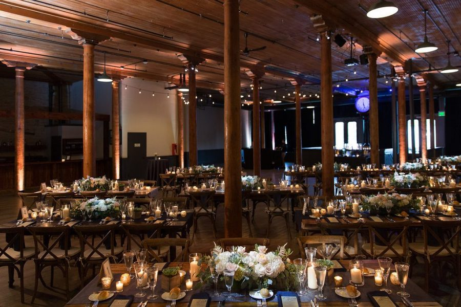 Wedding area beautifully decorated with lots of candles, low centerpieces of flowers and hanging lights