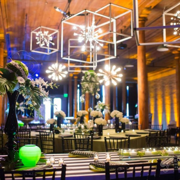 Reception with hanging square framed chandeliers and modern lights. Tables accent colors of green, gray and white.