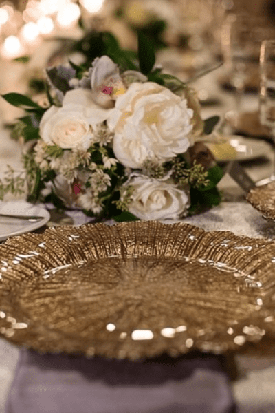 Decorated wedding table with gold charger and centerpieces