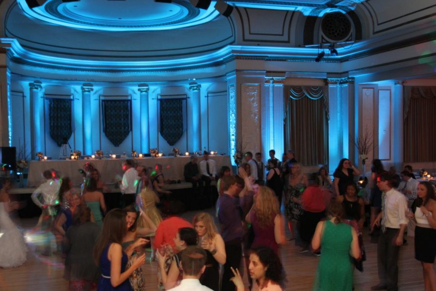 Dramatic up lighting with guest dancing in forefront at wedding reception with music by The Wedding DJay