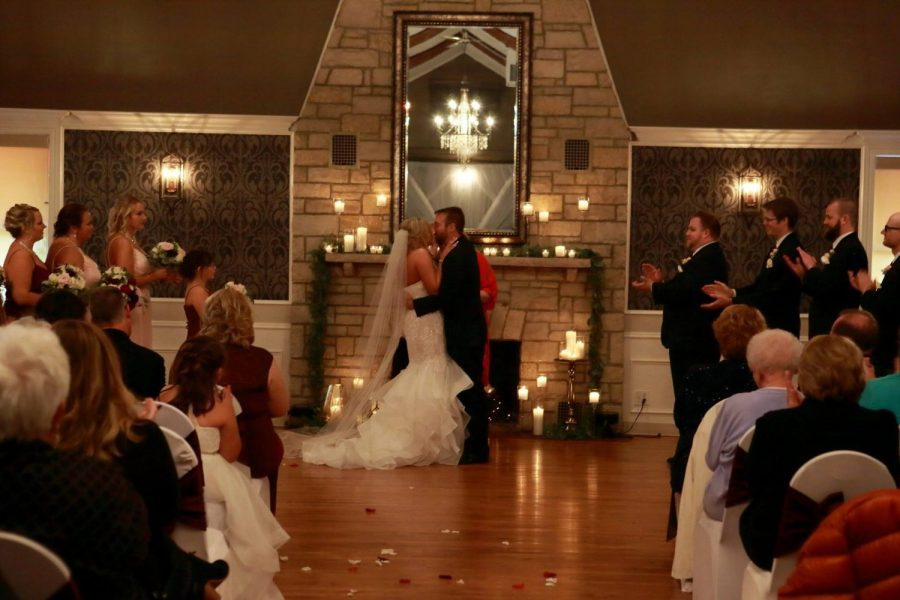 Bride and groom kissing at the close of their candlelit wedding ceremony at Tuscan Hall Banquet Center in Waukesha, WI