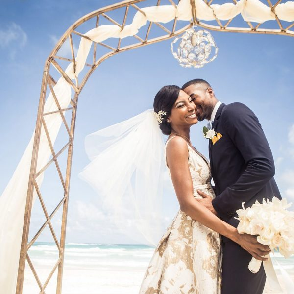Couple getting married under arch on ocean front