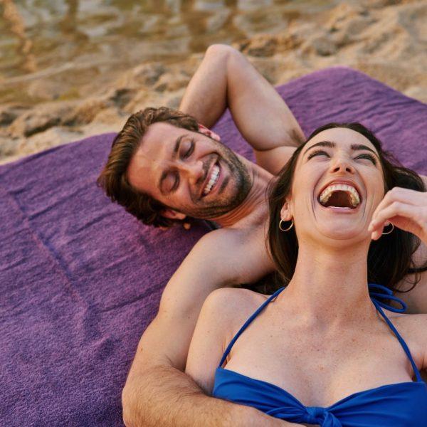 Honeymooners laughing on beach