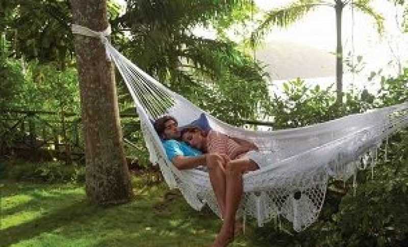Couple laying together on hammock off beach area