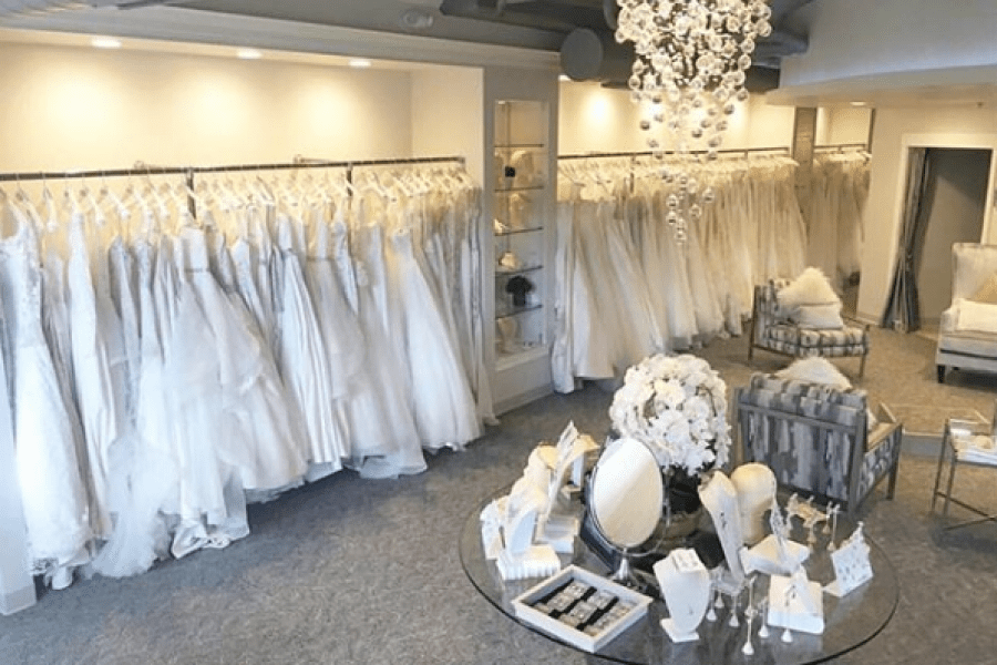 shows inside of White Dress with accessories and row of Bridal Gowns in background