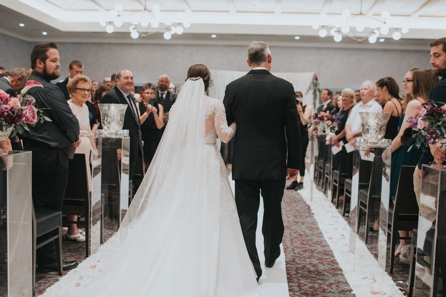 Bride being walked down the aisle at her Kimpton-Journeyman Hotel wedding ceremony