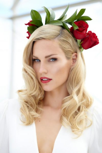 Beautifully done makeup and hair with red accent flowers