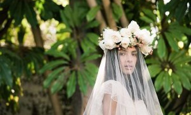 professional hair and makeup for bride in outside greenery backdrop