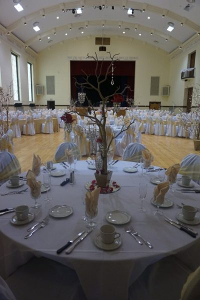 Table Setting with white and gold colors for wedding reception in beautiful ballroom