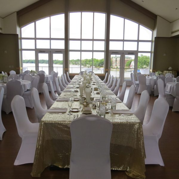 Wedding reception head with white fitted chair covers overlooking Lac La Belle at the The Oconomowoc Community Center