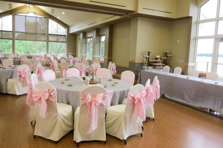 Wedding reception with white chair cover and pink ties at The Oconomowoc Community Center