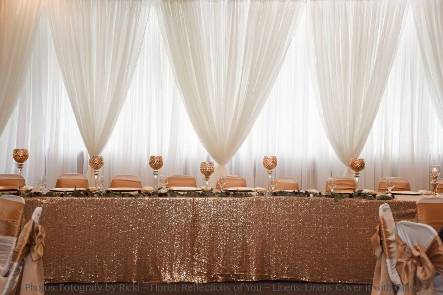 Beautiful head table with white sheer draping, shimmery peach table covering, with same accent color for goblets and chair ties.