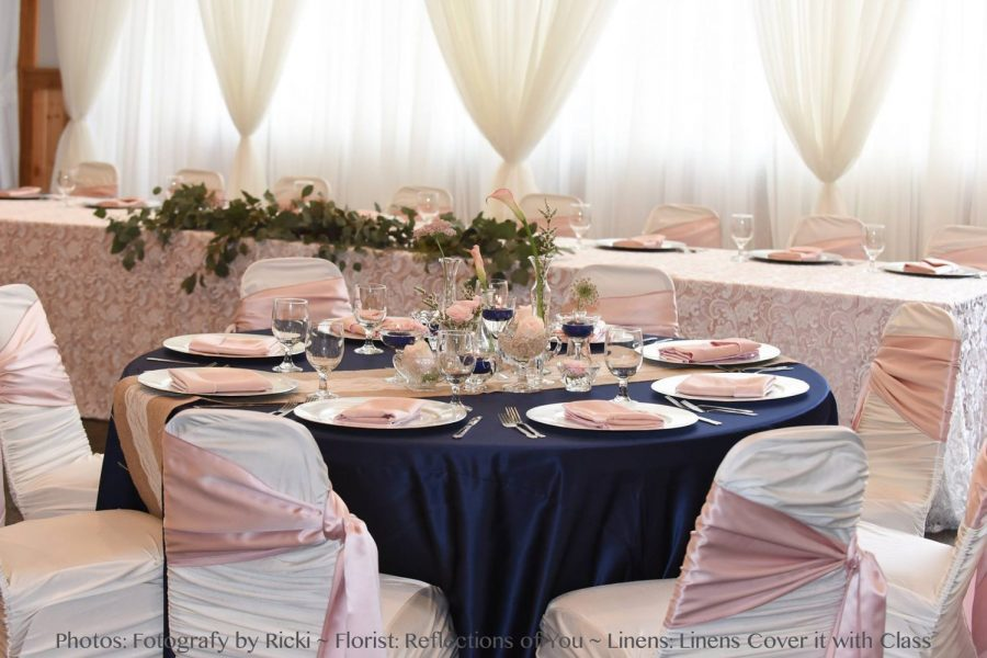 Cover It With Class decorated wedding reception with deep blue and soft pink color scheme, greenery and beautiful centerpieces