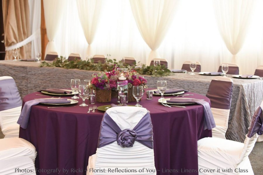 Beautifully decorated reception with purples, grays and cream sheer draping behind head table.