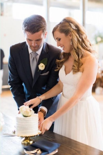 Bride and groom cutting cake on vintage cake plate rental