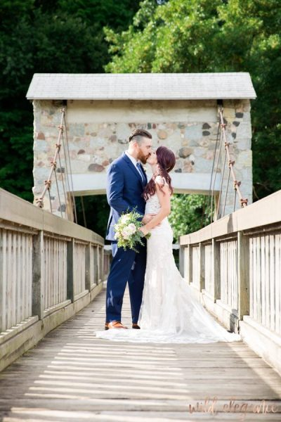 Bride and groom standing with bridal bouquet on wood bride with stone archway in background