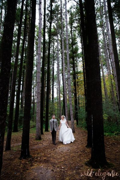 Bride and groom walking through tall trees