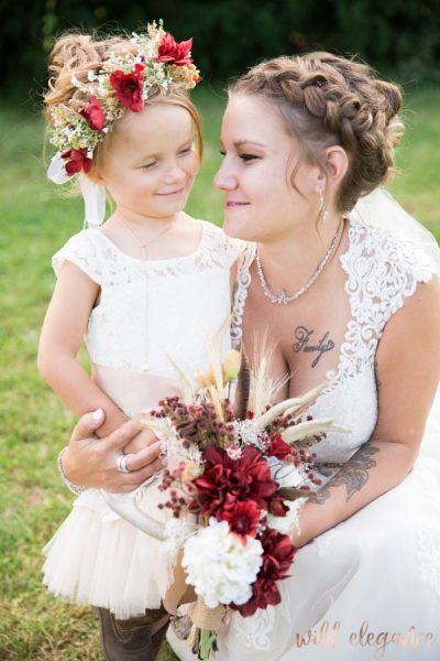 adorable bride and flower-girl image with red and white flowers.