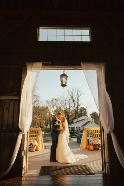 Bride and groom embrace on patio