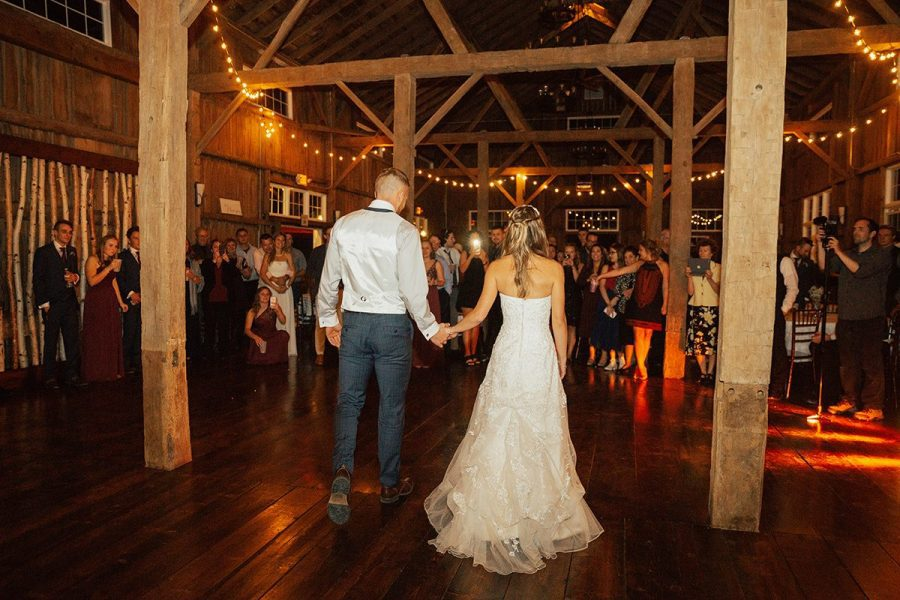 Bride and groom walk hand in hand onto the dance floor at Barn wedding