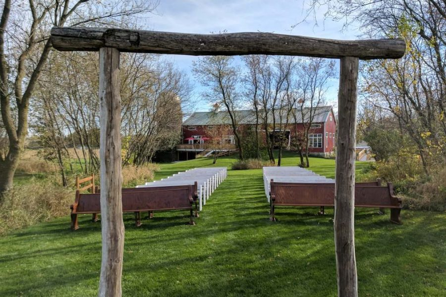 Wooden pews and arch create the perfect ceremony space at the Cupola in Oconomowoc, WI