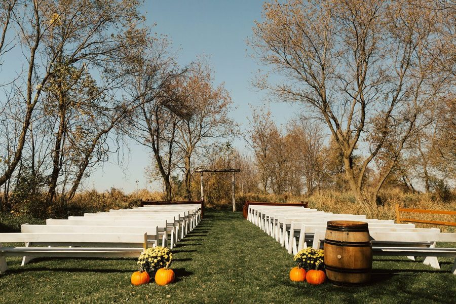 Outdoor fall wedding ceremony with white pews