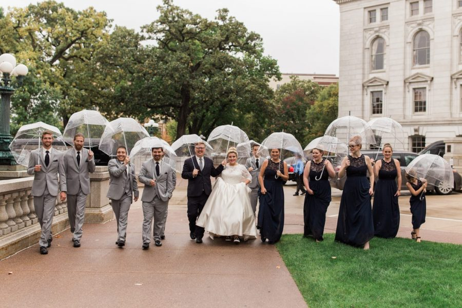 Wedding party walking in the rain with clear umbrellas | CREAM CITY WEDDINGS