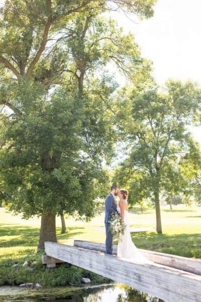 Bride and groom embrace on golf bridge at the Club at Lac La Belle