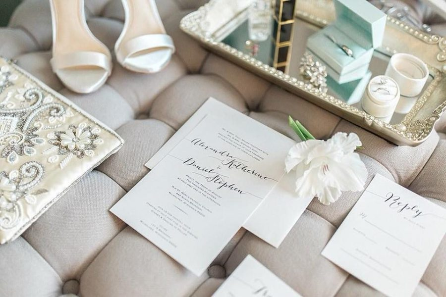Classic wedding invitation suite laid out on beige button tufted chaise lounge