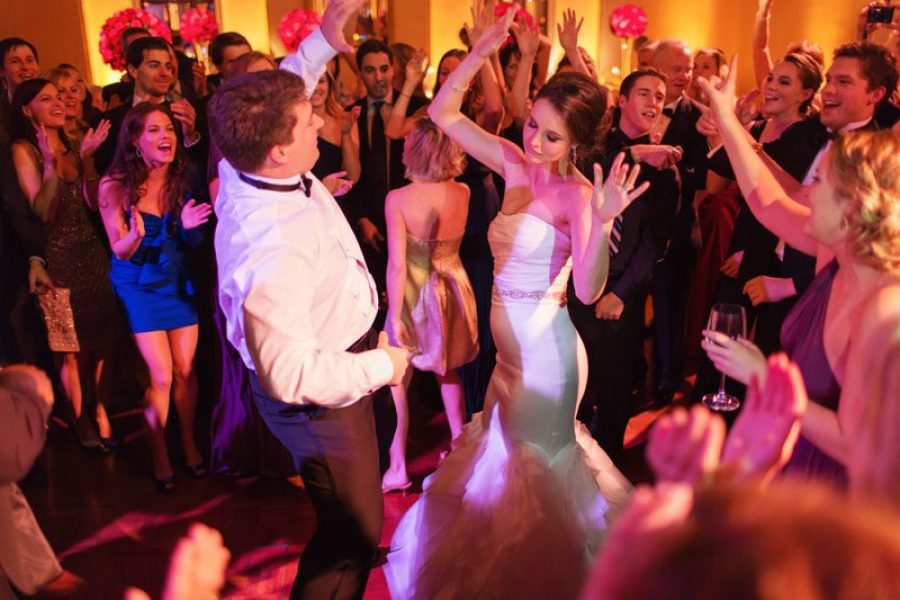bride and groom dancing on filled dance floor at wedding reception