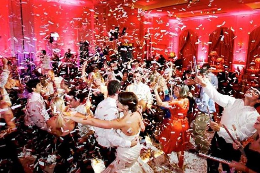 confetti filled air with wedding guests dancing