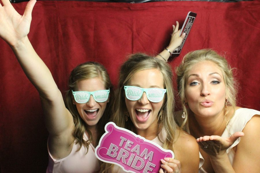 girls having fun in photo booth at wedding reception
