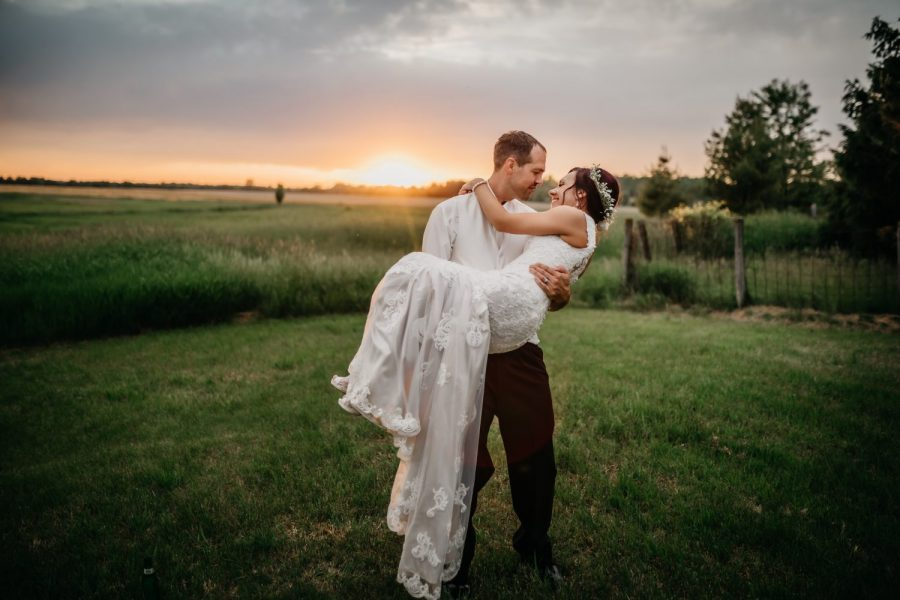 Groom carries his bride in country setting at sunset