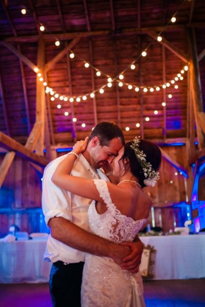 Bride and groom dance under the twinkling lights at a rustic barn wedding reception at the Farmstead in Delavan, WI