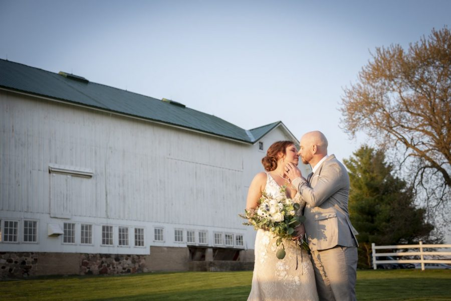 Bride and groom pose outside large white rustic barn- The Farmstead in Delavan, WI