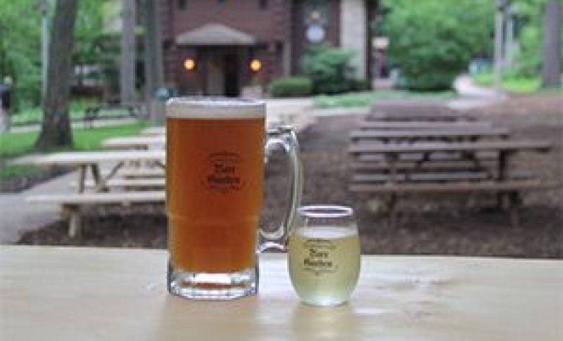 Full mug of beer in forefront of Hubbard Park Beer Garden